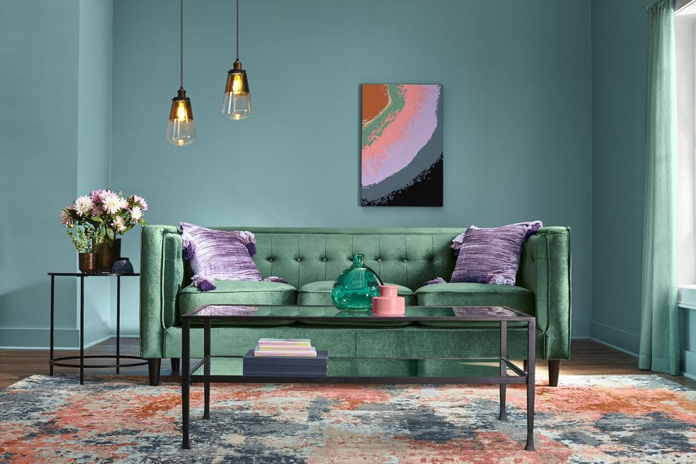 Sitting room with soft sea foam green walls and matching couch.