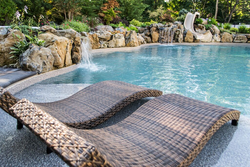 Woven lounge chairs with a curvy base by the poolside.