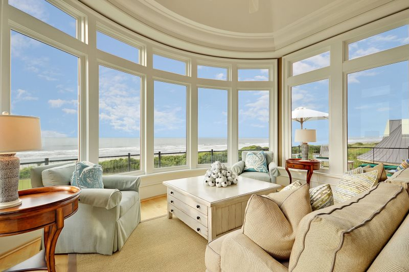 Large sitting room with giant windows showing a beach view.