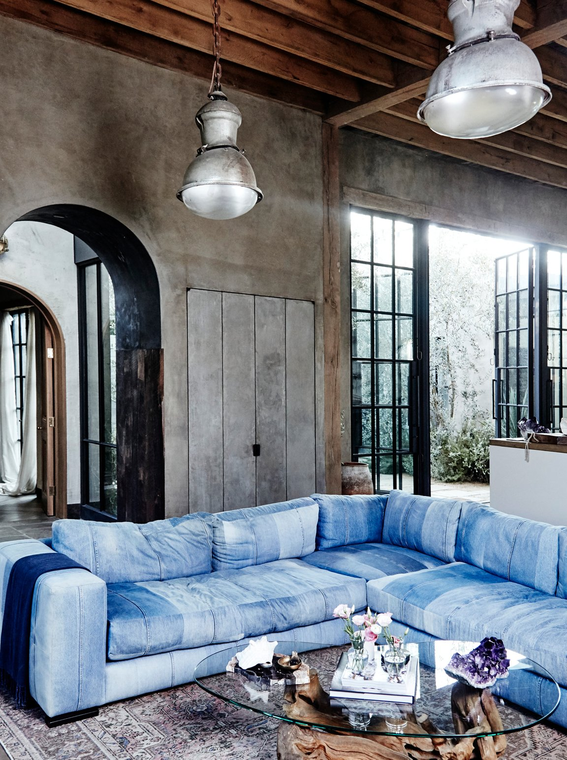 Industrial loft apartment featuring a large blue denim sectional couch.