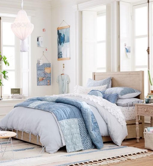 Well lit bedroom with blue denim blankets and pillows.