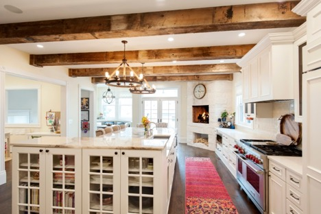 Luxurious white kitchen with wooden beams across the ceiling.