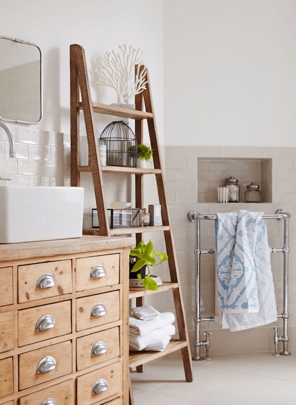 Ladder used as storage space in a bathroom.
