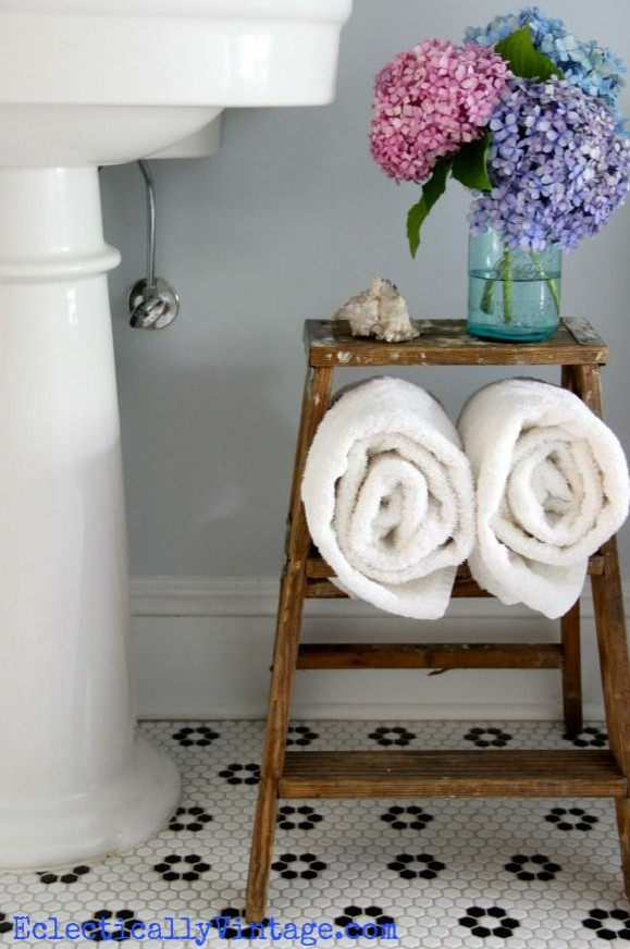 Towels folded on a ladder step stool in a bathroom.