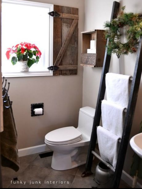 Wooden ladder in a bathroom with folded towels hanging from it.