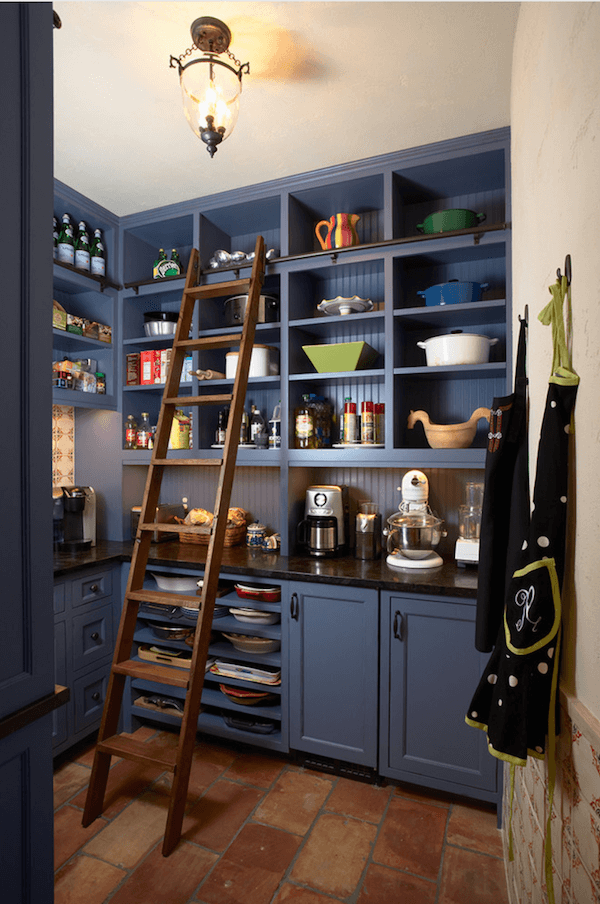Blue kitchen cabinets with a tall wooden ladder to access the top shelves.