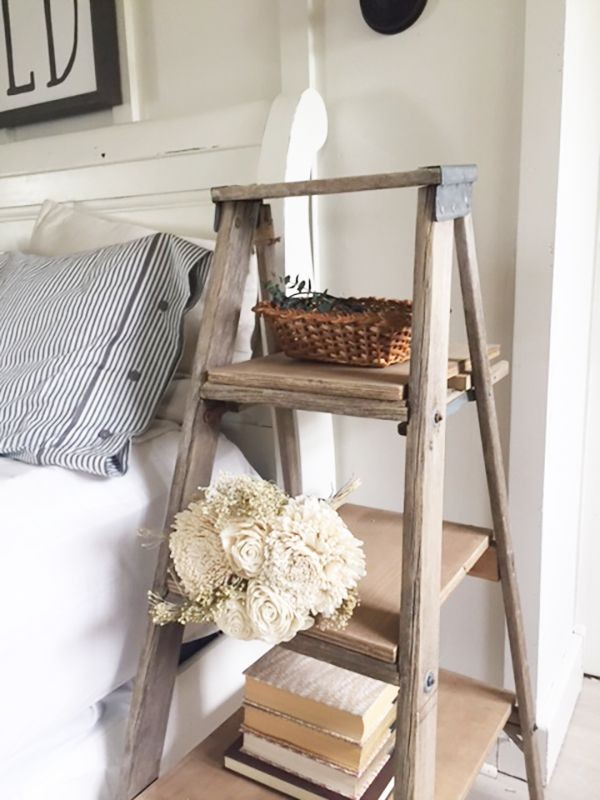 Wooden ladder acting as a nightstand next to a bed.