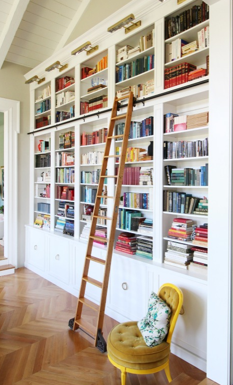 Giant wall covered in bookshelves with a tall ladder on wheels.