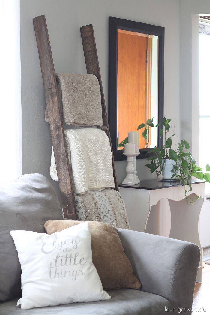 Wooden ladder in a living room holding folded blankets.