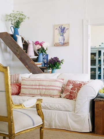 Wooden ladder holding up flowers behind a couch in a living room.