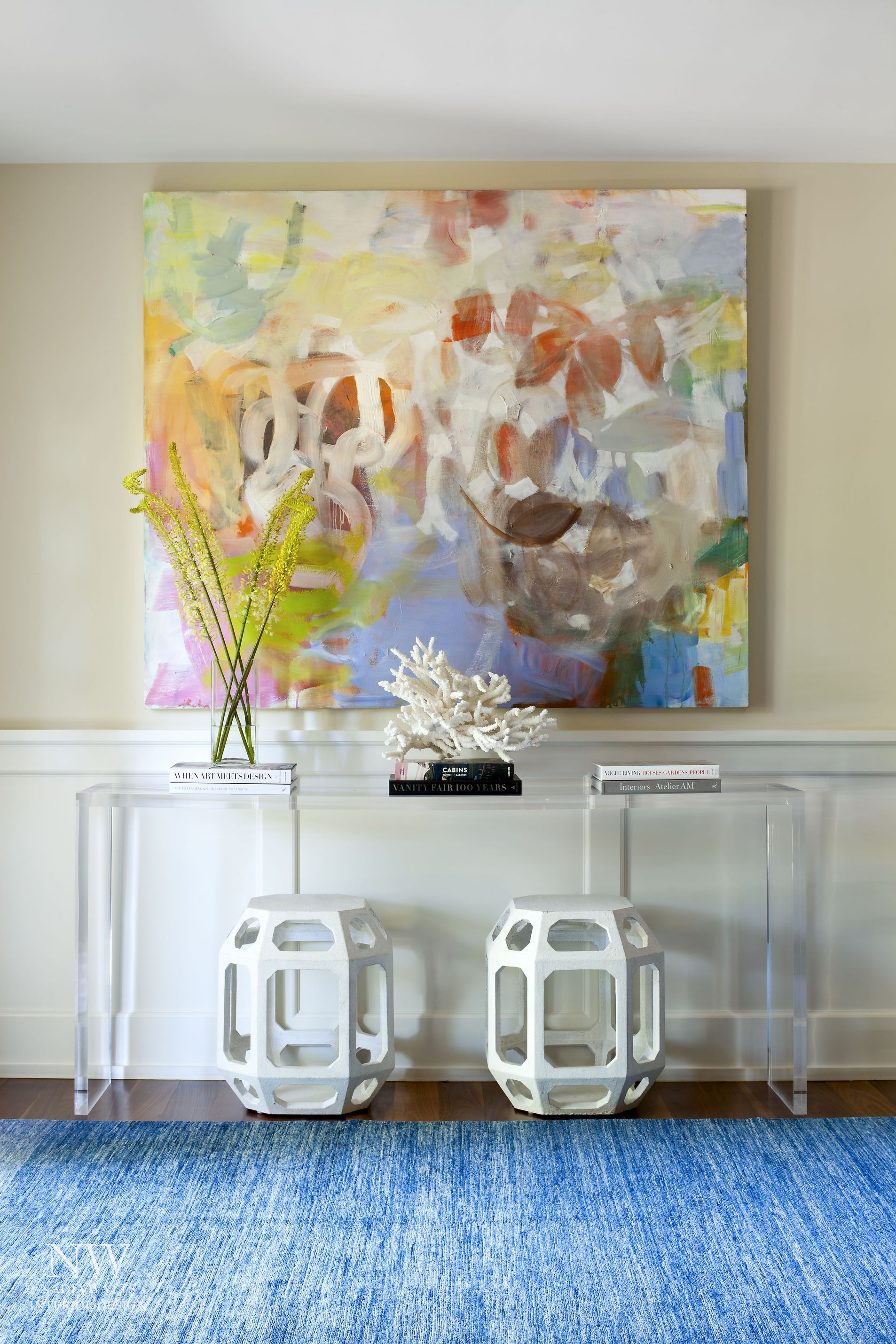 Entryway of a home with a beautiful painting hanging above an occasional table.