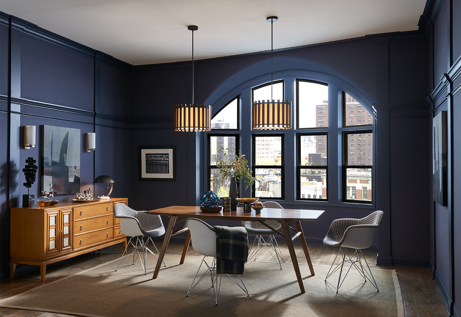 Dark blue dining room with city showing through large windows.
