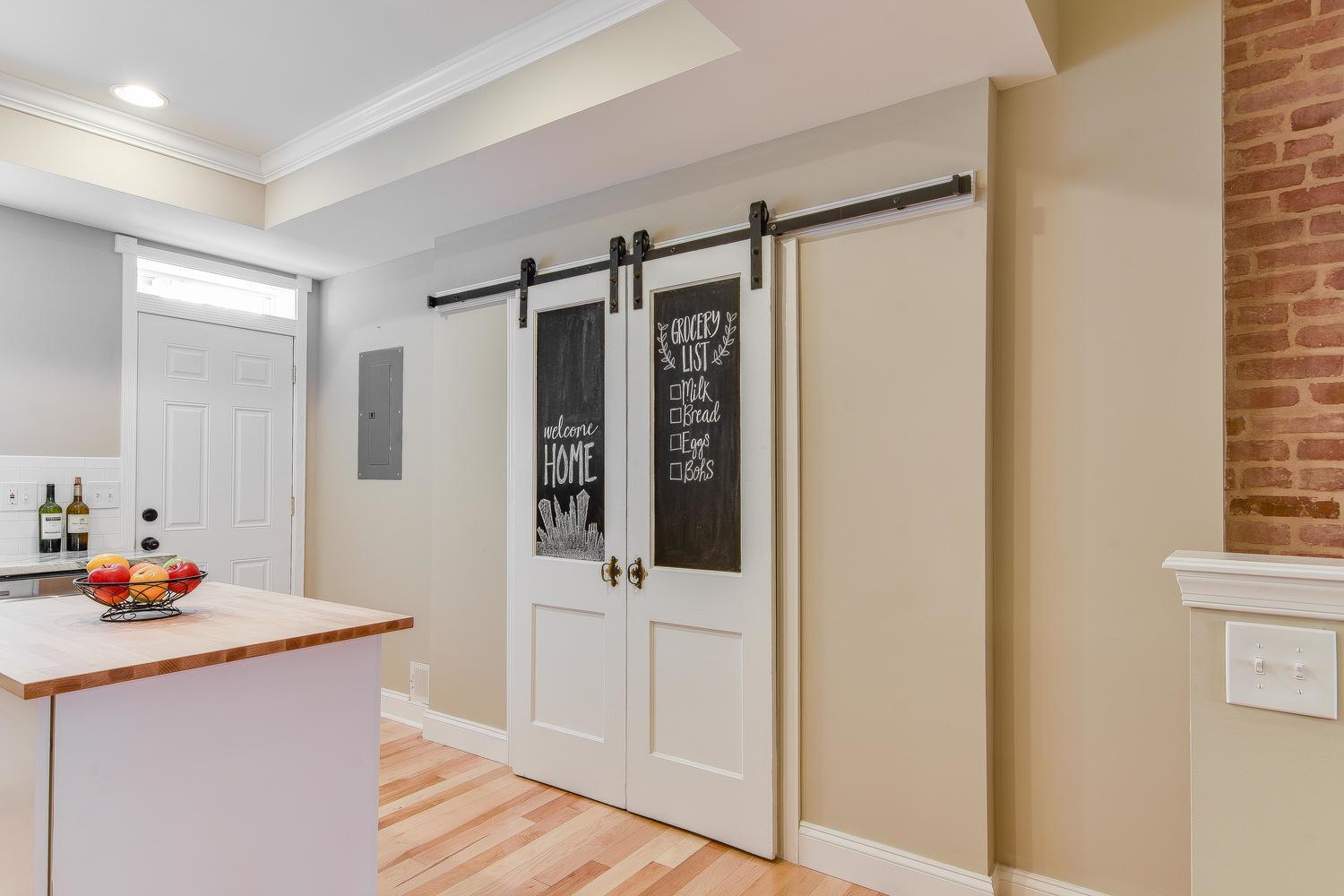White barn door-style pantry doors in a kitchen