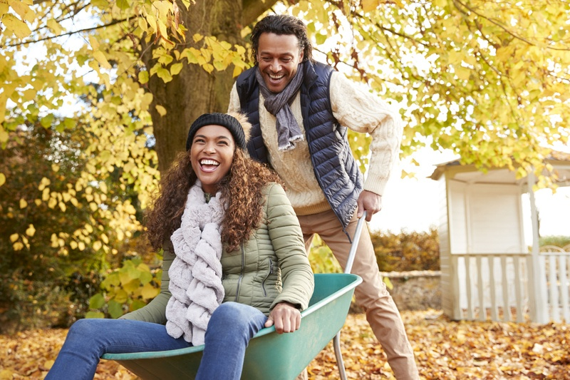 Man pushing his girlfriend in a wheel barrow during the fall season