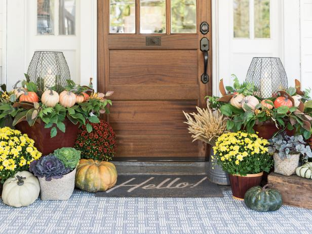 Outdoor entrance of a home with fall decor outside.