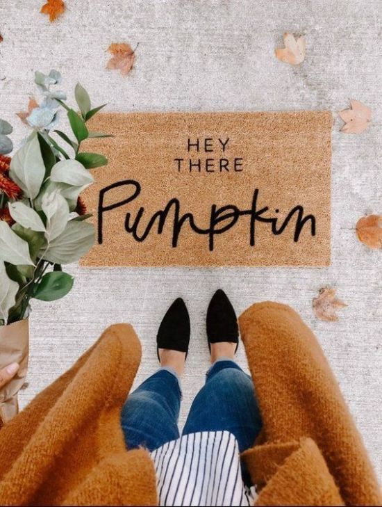 Woman in Fall outfit standing over Fall themed doormat