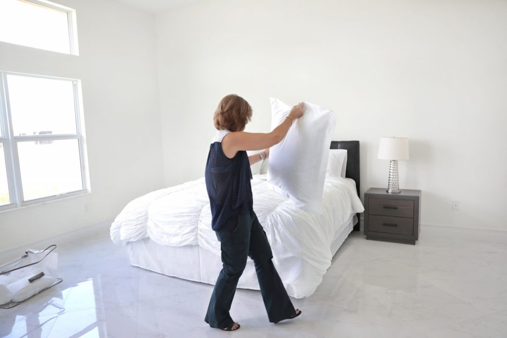 Woman using home staging techniques in a bedroom