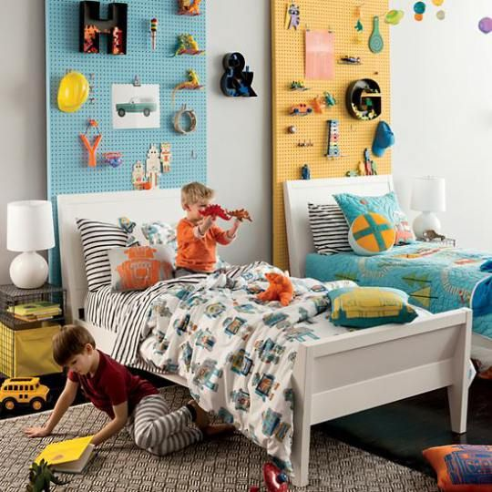 Twin beds in a kids room with peg boards used for storage on the walls behind them