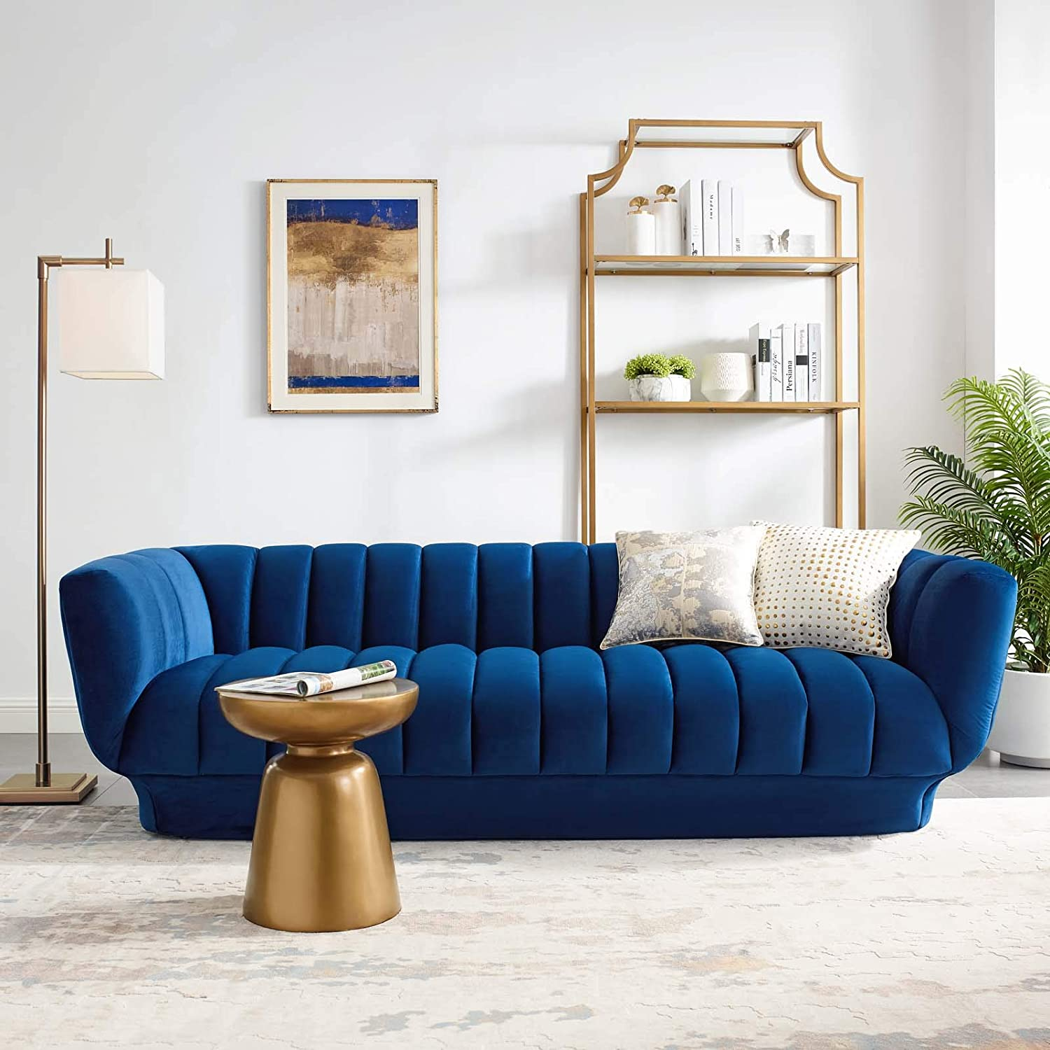 blue couch with gold furniture accents around it