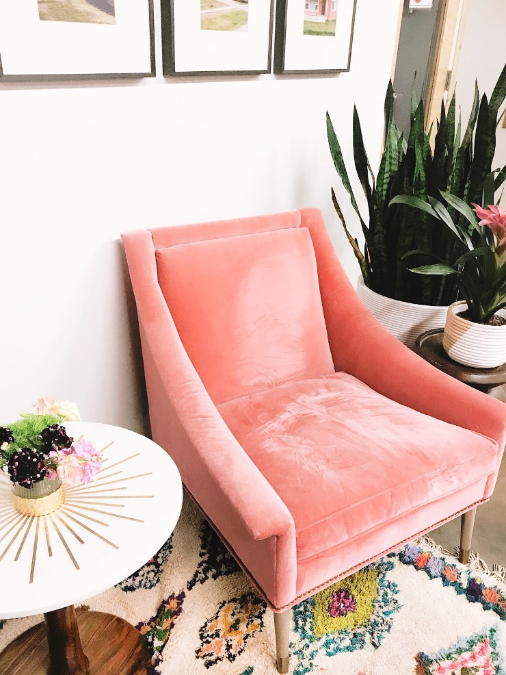 Corner of a room elegantly decorated with a velvet chair, side table, rug, and green plants