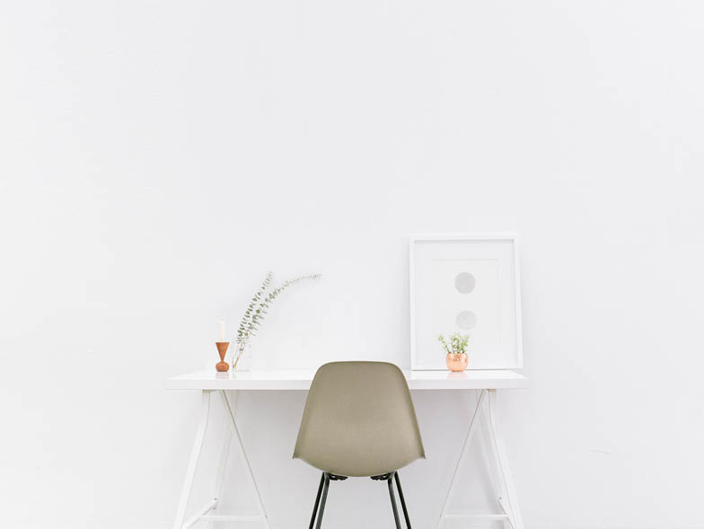 White room with white desk and olive green chair