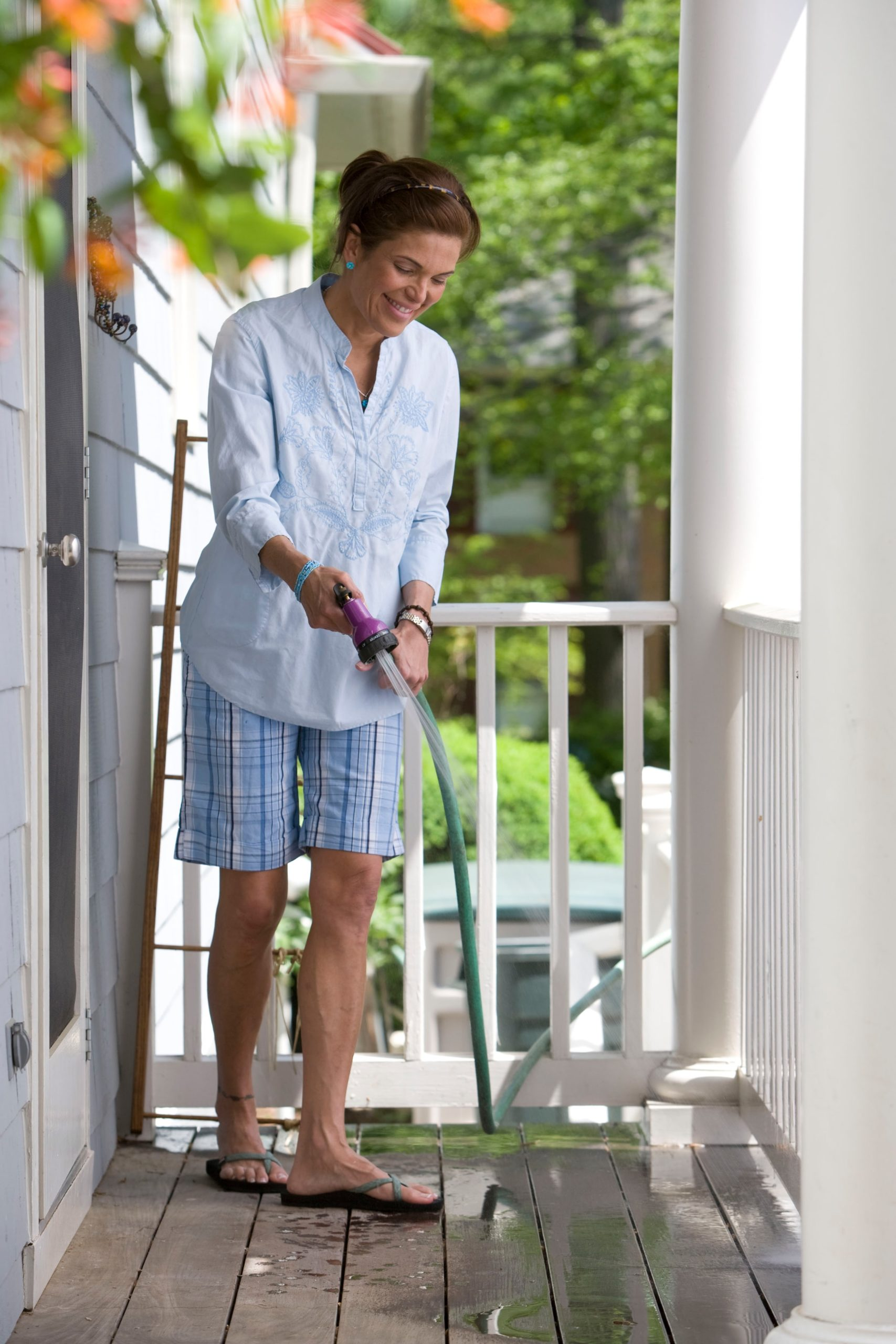 Woman using watering hose on front porch