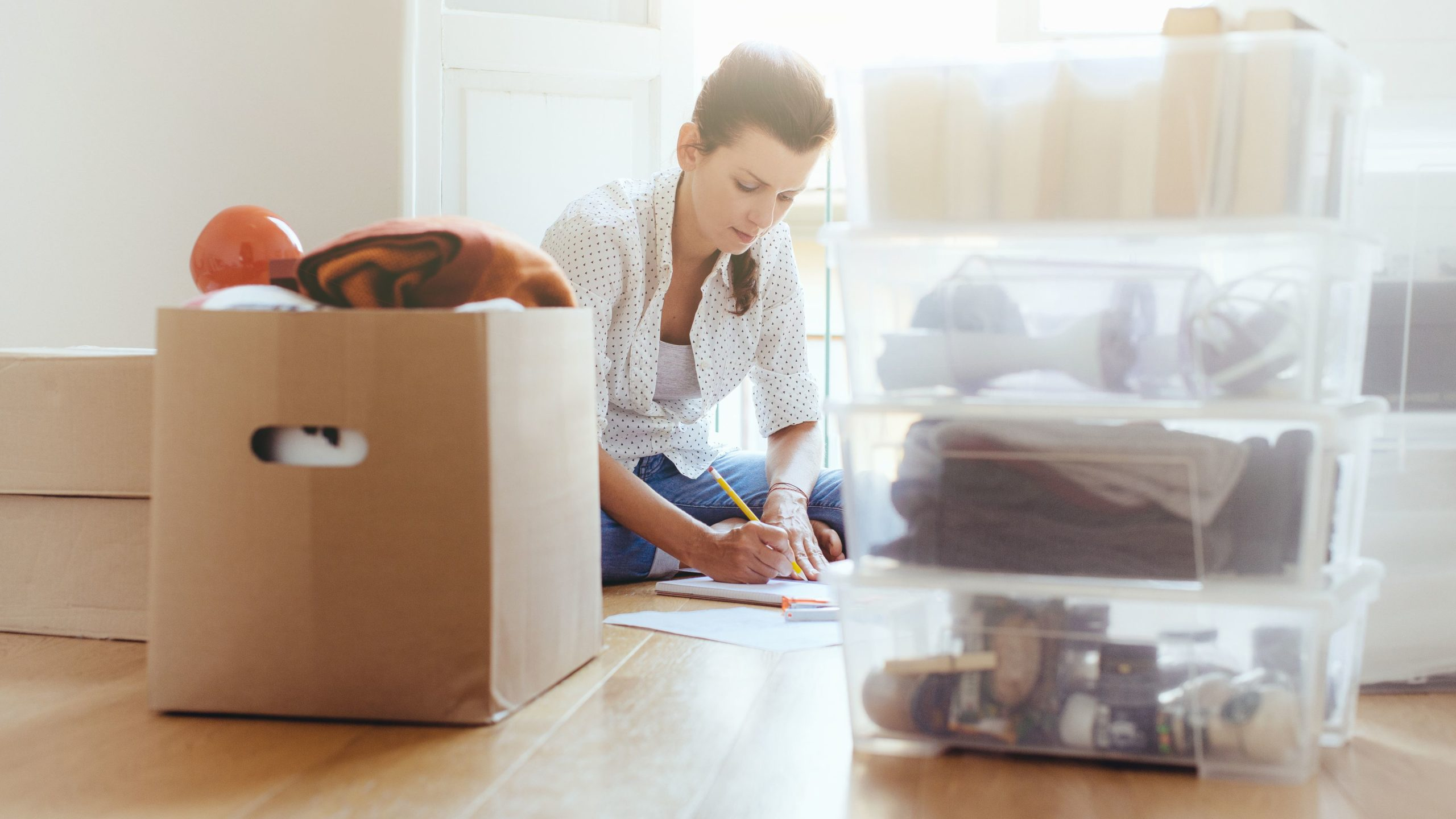 Woman filling moving boxes on the floor