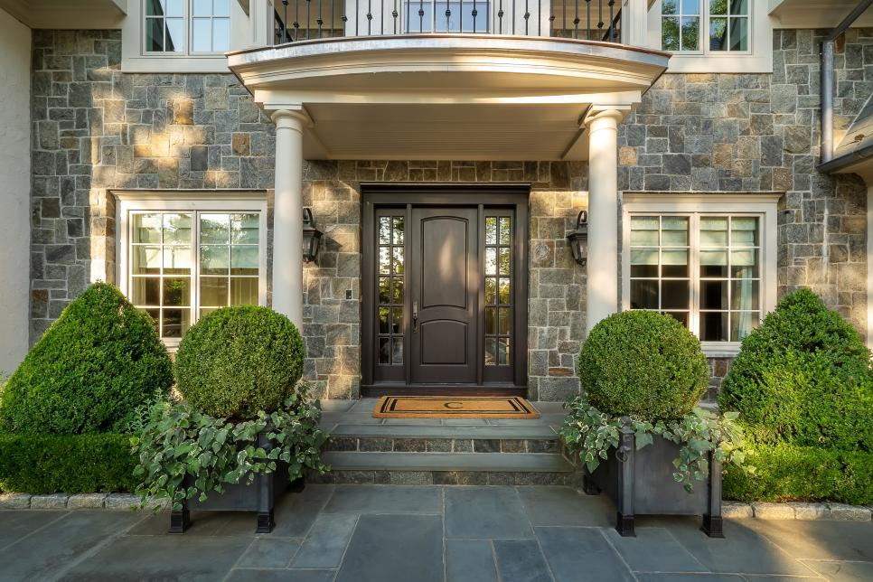 Boxwood plants in front of an elegant home