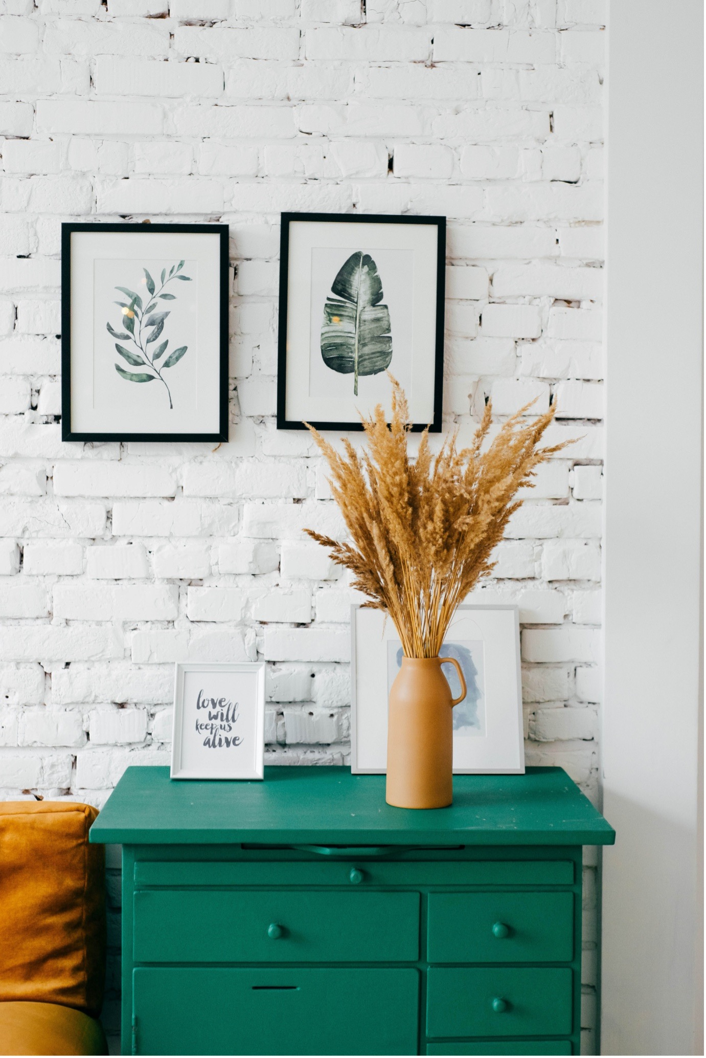 Bed side table painted green with white brick wall behind it.